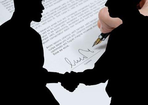 Zwei Geschäftsleute schütteln sich nach Unterzeichnung einer Anzahlungsbürgschaft die Hände