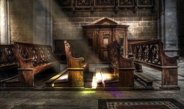 Innenraum einer Kirche mit Kirchbänken; Sonnenstrahlen erzeugen Licht: Die Bank für Kirche und Caritas eG ist eine Spezialbank für katholische Einrichtungen.