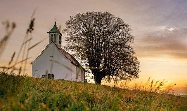 Kirche auf einem Feld bei Sonnenuntergang: Kirchenbanken unterstützen vor allem kirchliche und karitative Einrichtungen finanziell