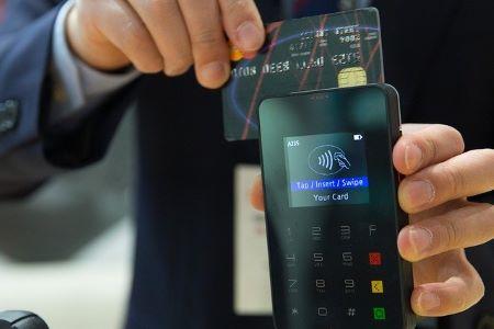 Mann, der gerade mit seiner Kreditkarte bezahlt: Wer viel einkauft, braucht auch mal einen günstigen Konsumkredit!