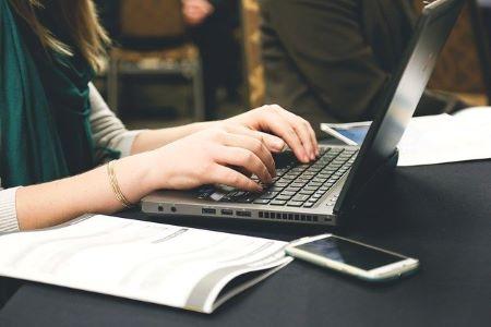 Angestellte im Öffentlichen Dienst am Laptop auf der Suche nach einem günstigen Kredit