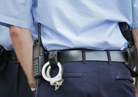 Polizeibeamter mit Handschellen und Dienstwaffe von hinten: Grundsätzlich erhalten Polisten ebenso flexible wie günstige Polizistenkredite!