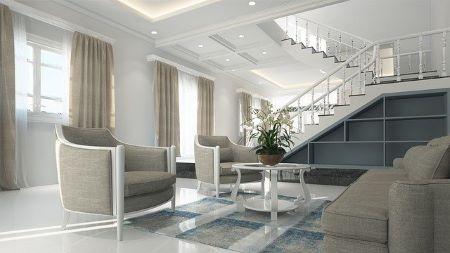 Schönes Wohnzimmer mit modernen Sitzmöglichkeiten und einem Tisch in der Mitte, im Hintergrund eine Treppe: Möbelfinanzierung und Möbelkredit machen den Kauf schöner Einrichtungsgegenstände möglich!