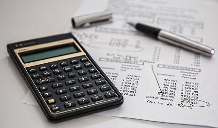 Taschenrechner und Stift auf einem Blatt Papier mit Zahlen: Lebensversicherungen können beliehen werden, um ein Policendarlehen zu erhalten
