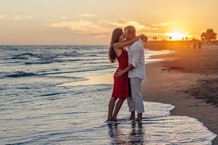 Pärchen, das bei Sonnenuntergang am Strand küssend seine Reise genießt: Eine Traumreise kann durch Aufnahme eines Reisekredits auf Raten finanziert werden!