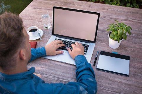 Junger Unternehmer an seinem Laptop auf der Suche nach einem günstigen Unternehmerkredit