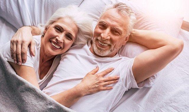 Älteres Paar, das gemeinsam glücklich in einem weißen Bett liegt: Auch ältere Menschen können einen Kredit für Rentner über 70 Jahren erhalten!
