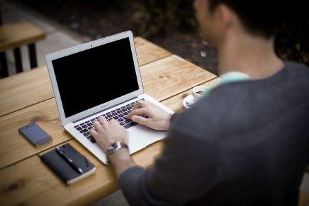 Junger Mann am Laptop: Wenn Sie einen 25000 Euro Kredit benötigen, können Sie diesen heutzutage ganz leicht online beantragen!