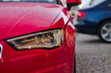 Linker Scheinwerfer eines roten Neuwagens: Neue Autos werden gern mit Hilfe einer Ballonfinanzierung finanziert.