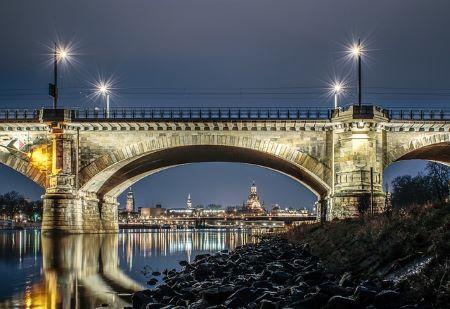Brücke und Stadt Dresden im Hintergrund: Überbücken Sie finanzielle Engpässe mit Hilfe eines im Leihhaus Dresden aufgenommenen Pfandkredits