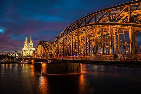 Nachtaufnahme des beleuchteten Kölner Dom und der Kölner Rhein-Brücke: Wenn Sie in Köln schnell Geld benötigen, könnten Sie einem Leihhaus Köln einen Besuch abstatten!