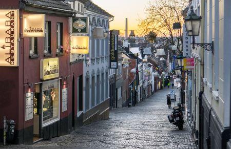 Straße mit Häusern und Restaurants in Mönchenglachbach: Solltest du einen Sofortkredit benötigen, hast du die Möglichkeit, einen solchen in einem Leihhaus Mönchengladbach zu erhalten!