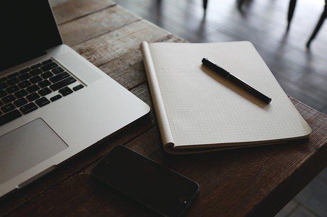 Smartphone, Block, Stift und Laptop auf einem Bürotisch: Wenn Sie schnell und unkompliziert einen 100000 Euro Kredit benötigen, dann können Sie heutzutage ganz bequem vom eigenen Schreibtisch aus ein faires 100000 Euro Darlehen online beantragen, nachdem Sie einen ausführlichen Kreditvergleich durchgeführt haben!