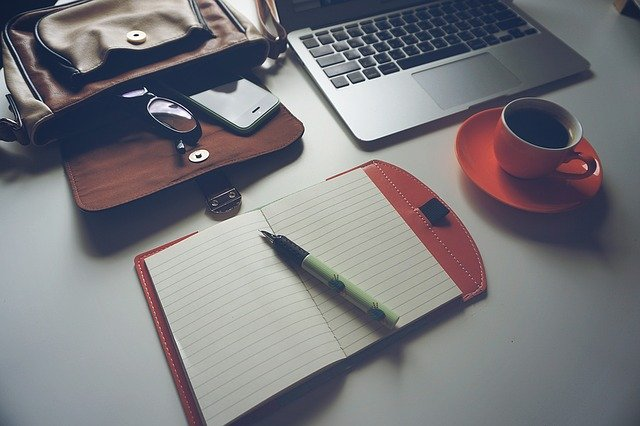 Notizblock, Stift, rote Tasse mit Kaffee, braune Tasche und grauer Laptop auf einem weißen Tisch: Wenn Sie Geld benötigen, können Sie noch heute online einen günstigen 11000 Euro Kredit beantragen!