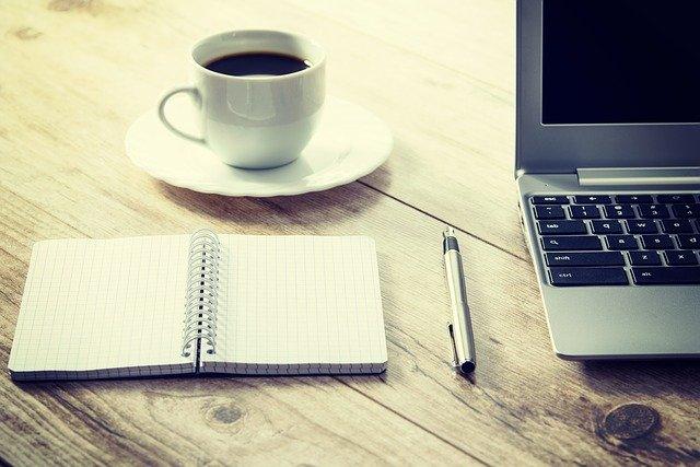 Notizbuch, Stift, Tasse Kaffee und Laptop auf einem Tisch aus Holz: Wenn Sie schnell 12000 Euro benötigen, können Sie heute ganz bequem von Zuhause aus einen günstigen 12000 Euro Kredit beantragen!