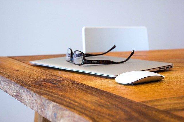 Graues Macbook, weiße Maus und schwarze Brille auf einem hölzernen Tisch: Wenn Sie 13000 Euro benötigen, können Sie noch heute einen günstigen 13000 Euro Kredit online beantragen!