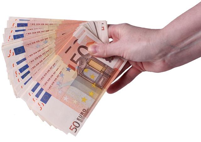 Rechte Hand, in der sich mehrere 50-Euro-Banknoten befinden: Wenn Sie schnell Geld benötigen, können Sie online einen günstigen 3500 Euro Kredit beantragen!