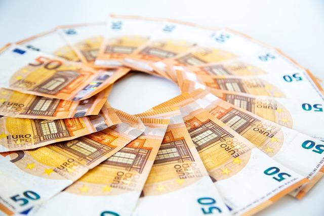 """50 Euro Geldscheine, im Kreis angeordnet, auf einem weißen Tisch liegend: Wenn Sie ein paar """"Fuffis"""" benötigen, können Sie ganz bequem von Zuhause aus noch heute einen 4000 Euro Kredit beantragen!"""
