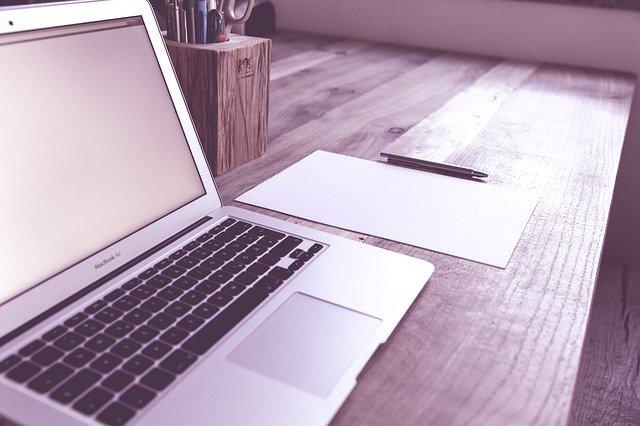 Macbook, weißes Blatt Papier und Stift auf einem Schreibtisch: Sie benötigen einen günstigen 40000 Euro Kredit? Beantragen Sie diesen ganz bequem von Zuhause aus: online!