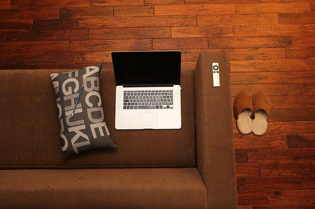 Laptop, Kissen und Fernbedienung auf einem Sofa, neben dem Sofa Pantoffeln: Wenn Sie einen 45000 Euro Kredit benötigen, können Sie diesen heute ganz bequem online vom eigenen Sofa aus beantragen!