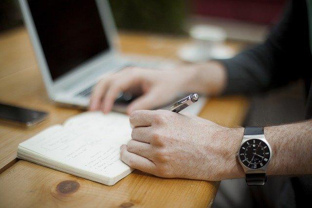 Mann an seinem Schreibtisch, etwas in sein Notizbuch schreibend, vor ihm ein Laptop: Wenn Sie ein günstiges 50000 Euro Darlehen benötigen, können Sie heute bequem vom eigenen Schreibtisch aus einen Kredit iHv 50000 Euro online beantragen!