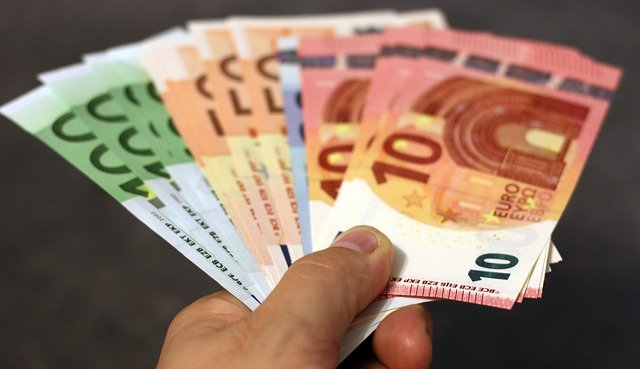 Linke Hand, die verschiedene Euro-Geldscheine hält: Wenn Sie schnell Geld benötigen, können Sie noch heute einen günstigen 5500 Euro Kredit online beantragen!