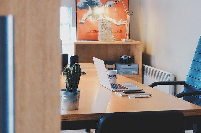 Arbeitszimmer mit Schreibtisch und Bürostuhl, auf dem Tisch Laptop, Tasse, Notizbuch, Pflanze und Co.: Wenn Sie einen günstigen 60000 Euro Kredit benötigen, sollten Sie unbedingt einen Online-Kreditvergleich durchführen!