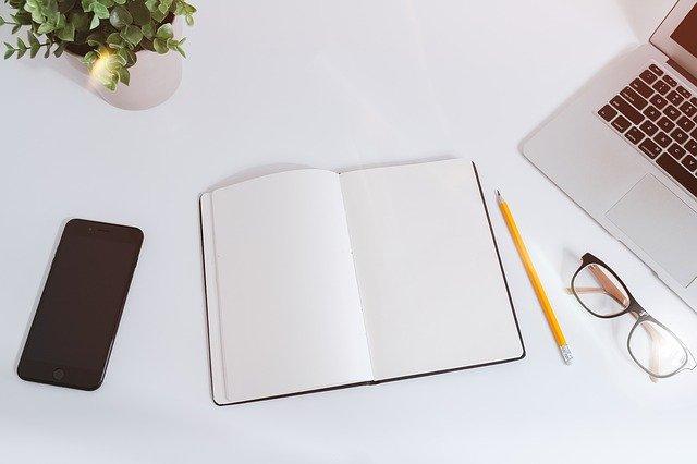 Smartphone, Pflanze, Notizbuch, Bleistift, Brille und Laptop auf einem weißen Tisch: Wenn Sie ein günstiges 85000 Euro Darlehen benötigen, dann können Sie heutzutage ganz leicht und unkompliziert einen fairen 85000 Euro Kredit online beantragen!