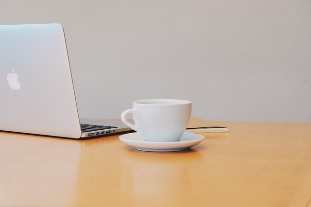 Weiße Tasse mit Kaffee. Notizbuch und Macbook auf einem Schreibtisch: Wenn Sie ein größeres Darlehen aufnehmen möchten, dann können Sie noch heute ganz bequem von Zuhause aus einen günstigen 90000 Euro Kredit online beantragen!