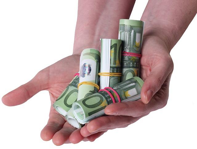 Zwei Hände mit mehreren Bündeln 100-Euro-Banknoten: Seien Sie endlich wieder liquide, indem Sie einen günstigen 9500 Euro Kredit online beantragen!