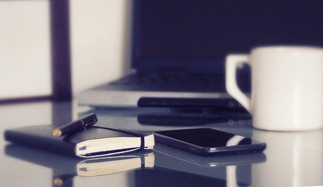 Notizbuch, Smartphone, Tasse und Laptop auf einem Tisch: Wenn Sie ein großes Darlehen benötigen, können Sie heute bequem online einen günstigen 95000 Euro Kredit beantragen!