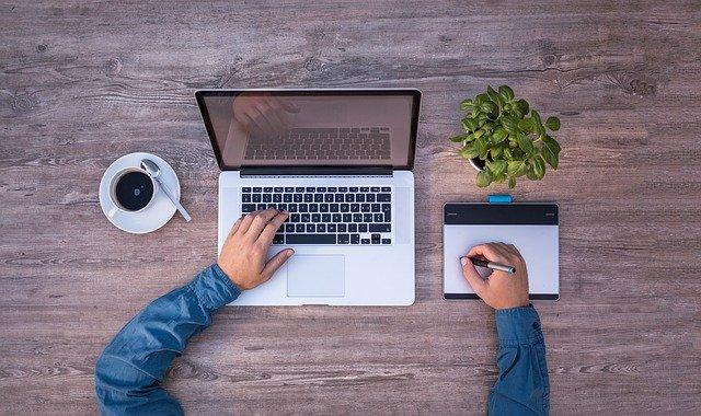 Tasse Kaffee, Laptop, Pflanze und Notizbuch auf einem Tisch. Junger Mann mit Stift vor dem Laptop sitzend: Wenn Sie einen günstigen Kredit benötigen sollten, dann können Sie noch heute den Bank of Scotland Kredit online beantragen!