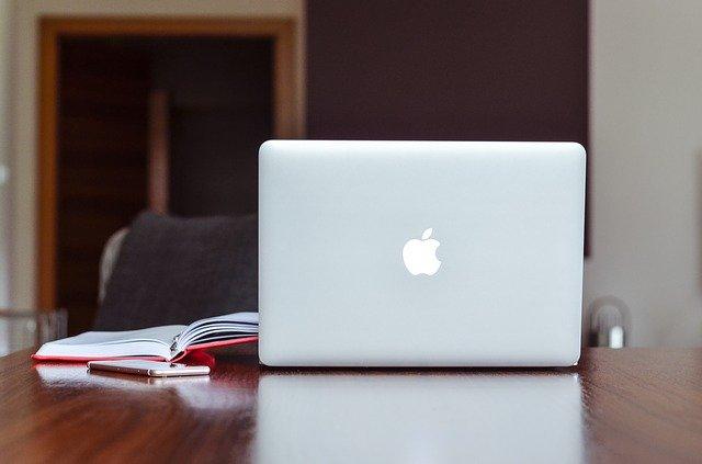 Macbook, rotes Notizbuch und Stift auf einem Schreibtisch; im Hintergrund ein Schreibtisch: Wenn Sie einen günstigen Privatkredit benötigen, dann schauen Sie sich doch mal den Bank of Scotland Ratenkredit genauer an!