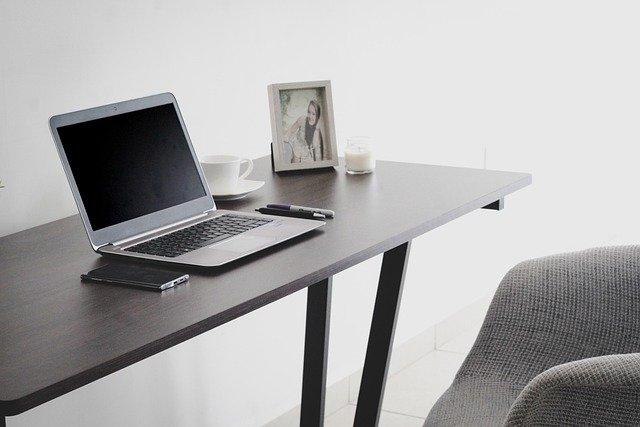 Smartphone, Laptop, Stift, Tasse Kaffee, weiße Kerze und Bild von einer Frau auf einem Schreibtisch: Wenn Sie schnellstmöglich einen Kredit für private Zwecke benötigen, können Sie noch heute bequem online den Barclaycard Ratenkredit beantragen!