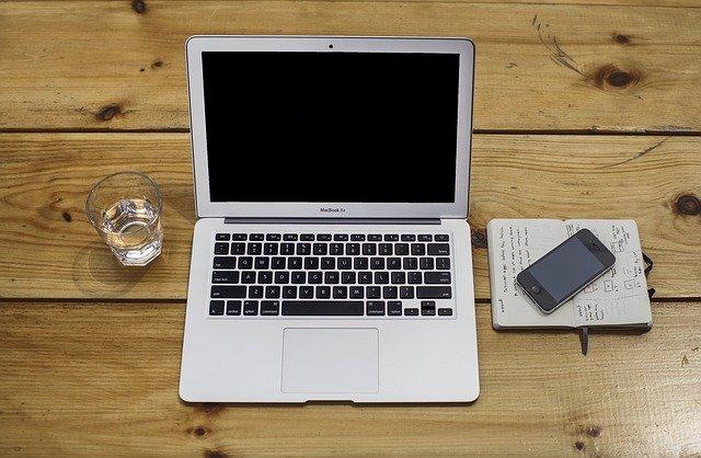 Glas Wasser, Macbook Air, Notizbuch und Smartphone auf einem Holztisch: Wenn Sie einen Kredit mit Sofortauszahlung benötigen, dann können Sie noch heute den Barclaycard Sofortkredit online beantragen!