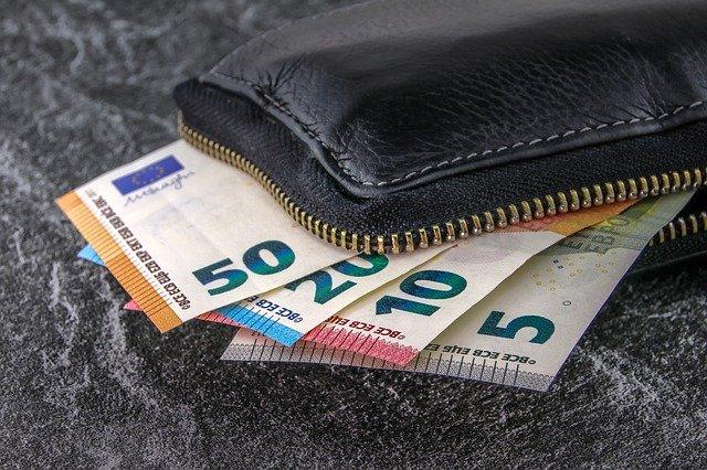 """Schwarze Geldbörse, und Euro-Banknoten, die aus derselben """"herauslugen"""": Wenn Sie Geld benötigen, können Sie beispielsweise einen günstigen Commerzbank Kredit aufnehmen!"""