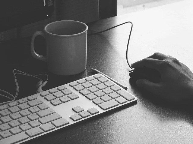 Tastatur, Tasse und Maus, die von einer Hand geführt wird, auf einem Bürotisch: Wenn Sie einen günstigen Ratenkredit mit Sofortauszahlung benötigen, dann können Sie noch heute den flexiblen Creditplus Kredit online beantragen!