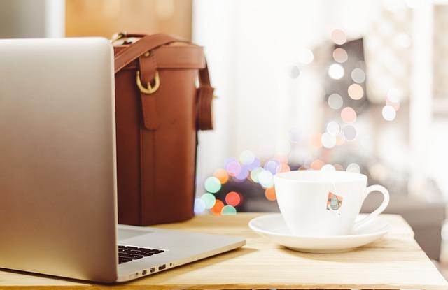 Grauer Laptop, weiße Tasse mit Tee und braune Tasche auf einem Schreibtisch: Wenn Sie einen Ratenkredit für private Zwecke benötigen, dann können Sie noch heute ein faires DKB Privatdarlehen bequem online beantragen!