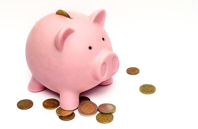Rosa Sparschwein und Münzen: Teure, bestehende Kredite können Sie mit Hilfe des DKB Umschuldungskredits vorzeitig ablösen, um Geld zu sparen!