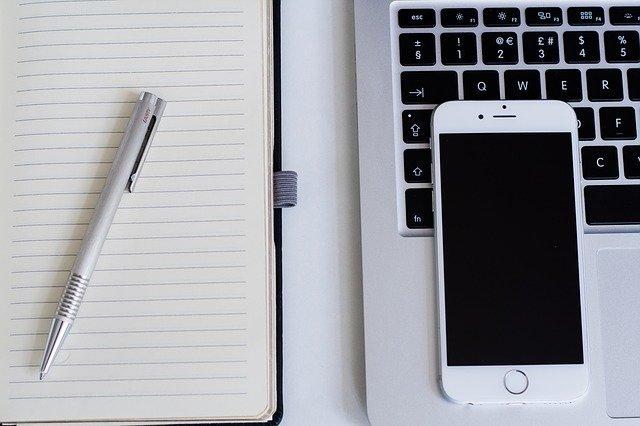 Notizbuch, Stift, Smartphone und Laptop auf einem Schreibtisch: Wenn Sie einen fairen Konsumkredit benötigen, dann können Sie bequem von Ihrem Schreibtisch aus den DSL Bank Privatkredit online beantragen!