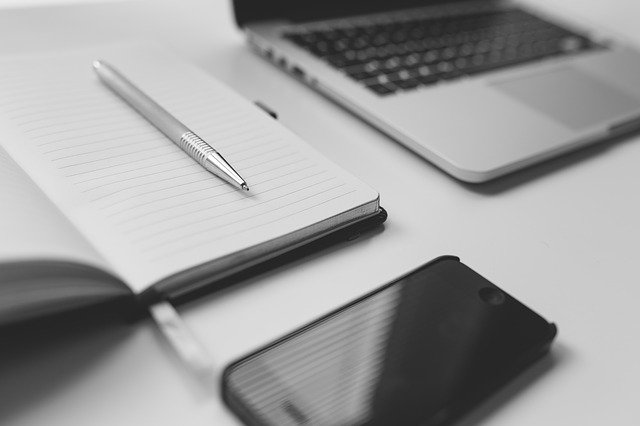 Notizbuch, Stift, Smartphone und Laptop auf einem Schreibtisch: Wenn Sie einen Online-Kredit beantragen möchten, ist der OYAK ANKER Bank Kredit evtl. genau das richtige Finanzprodukt für Sie!?