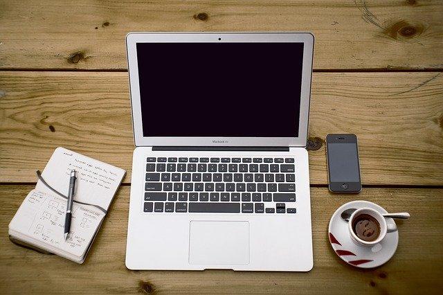 Notizblock mit Stift, Laptop, Smartphone und Tasse Kaffee auf einem Holztisch: Wenn Sie selbstständig sind und Ihr Geschäft ankurbeln möchten, kann Ihnen der günstige Postbank Business Kredit evtl. behilflich dabei sein!