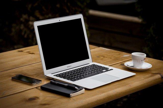 Laptop, Notizblock und Tasse Kaffee auf einem Holztisch: Wenn Sie Geld benötigen, können Sie den günstigen Postbank Kredit bequem online beantragen!