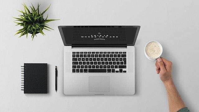 Laptop, Pflanze, Notizblock, Stift und eine Tasse Kaffee, die von einer Hand gehalten wird: Wenn Sie Geld benötigen, können Sie den günstigen Postbank Privatkredit bequem online beantragen!