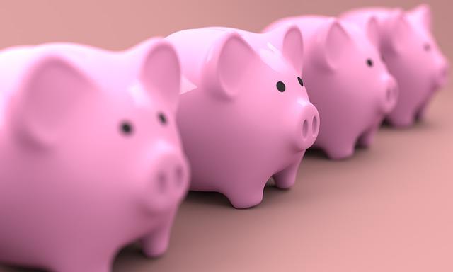 Vier rosa Sparschweinchen in einer Reihe: Sie möchten Ihre teuren Kredite ablösen und viel Geld sparen? Dann beantragen Sie noch heute den günstigen Postbank Umschuldungskredit online!