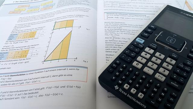 Taschenrechner auf einem aufgeschlagenen Mathematik-Buch: Wer die Zinsersparnis bei einer Umschuldung ausrechnen möchte, benötigt mathematisches Verständnis!