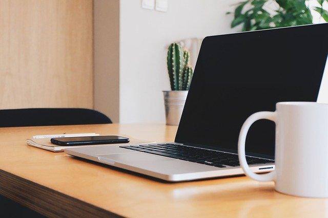 Laptop, Smartphone, weiße Tasse mit Kaffee auf einem Tisch, im Hintergrund grüne Pflanzen: Wenn Sie einen Ratenkredit benötigen, können Sie jetzt gern den günstigen Santander Privatkredit online beantragen!