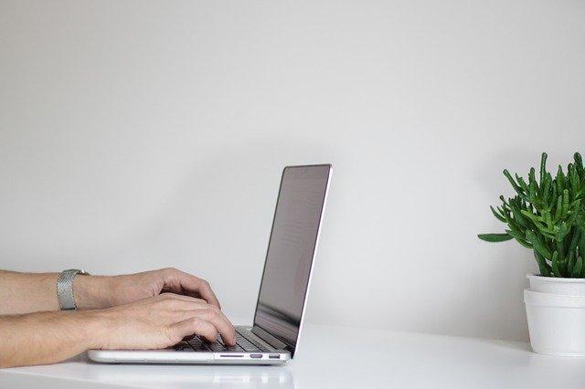 Männerhände, die die die Tastatur eines grauen Laptops betätigen: Wenn Sie einen Schnellkredit benötigen, wäre eventuell der günstige Santander Sofortkredit etwas für Sie!?