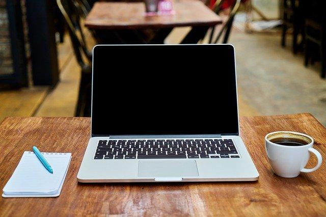 Notizblock und Stift, Laptop und Tasse Kaffee auf einem Tisch: Wenn Sie einen Kredit online beantragen möchten, wäre eventuell der flexible SWK Bank Kredit eine gute Option für Sie!?