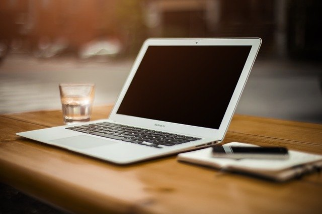 Weißer Laptop auf dem Tisch, daneben ein Glas Wasser, ein Notizblock und ein Stift: Beantragen Sie noch heute Ihren Targobank Kredit mit Wunschrate online!